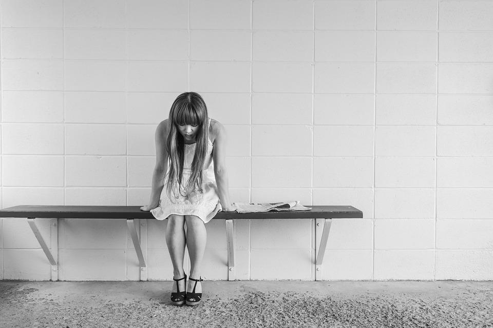 worried girl sitting on bench