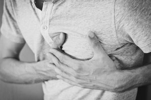 Man holding his chest having heart attack